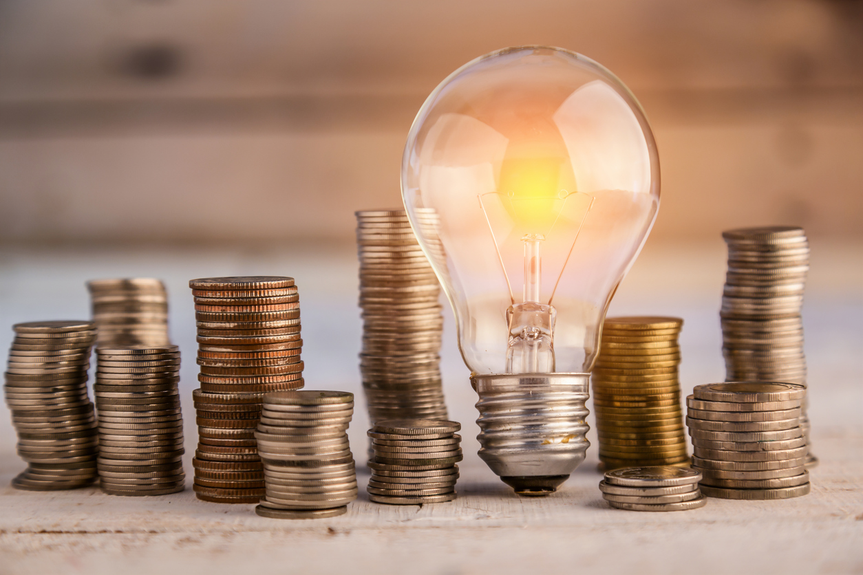 glowing light bulb among many coins